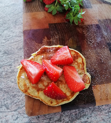 Buy stock photo Shot of strawberries served on a freshly made pancake