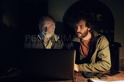 Buy stock photo Shot of a young man and his elderly father using a laptop together at home during the night