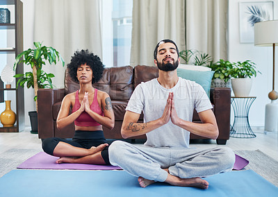 Buy stock photo Shot of a young couple practising yoga in their living room