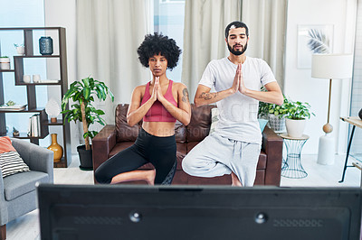 Buy stock photo Shot of a couple looking at the television while practising yoga at home