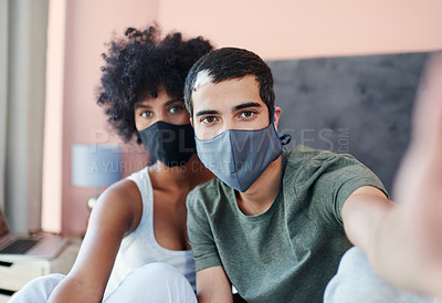 Buy stock photo Cropped shot of a young couple taking a selfie while wearing their masks