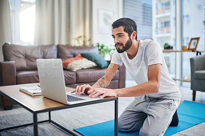Buy stock photo Shot of a man using his laptop while practising yoga at home