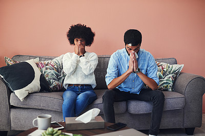Buy stock photo Shot of a young couple blowing their noses while sitting on the sofa at home