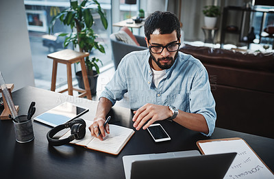 Buy stock photo Shot of a young man using his laptop while working from home