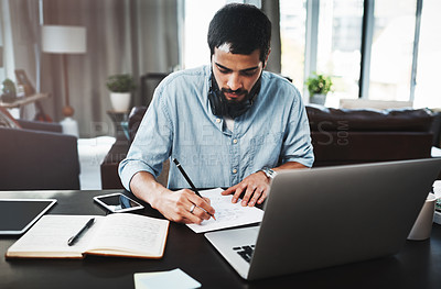 Buy stock photo Shot of a young man making notes while busy working from home