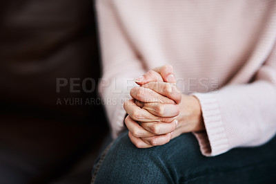 Buy stock photo Cropped shot of a woman sitting on a sofa and feeling anxious