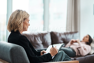 Buy stock photo Shot of a mature psychologist writing notes during a therapeutic session with her patient