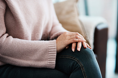 Buy stock photo Cropped shot of a woman sitting on a sofa at home
