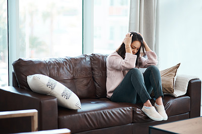 Buy stock photo Shot of a young woman experiencing mental anguish at home