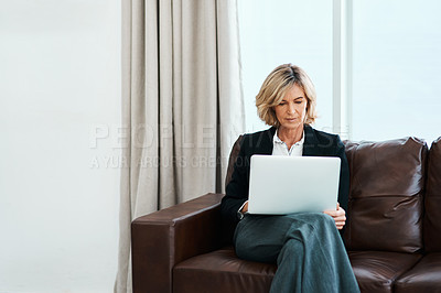 Buy stock photo Shot of a mature psychologist sitting on a sofa and using a laptop