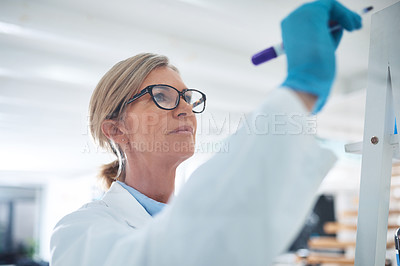 Buy stock photo Shot of a mature scientist writing notes on a glass wall in a lab