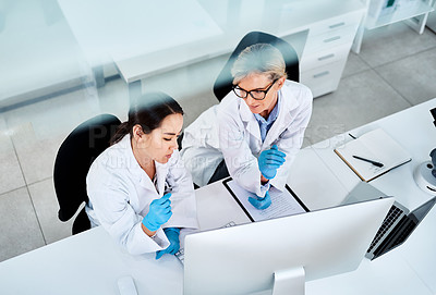 Buy stock photo Shot of two scientists working together on a computer in a lab