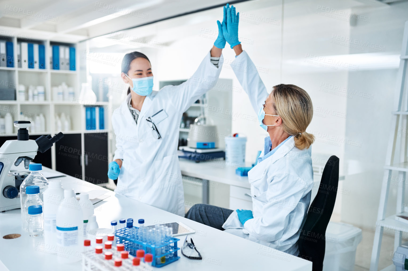 Buy stock photo Shot of two scientists giving each other a high five in a lab