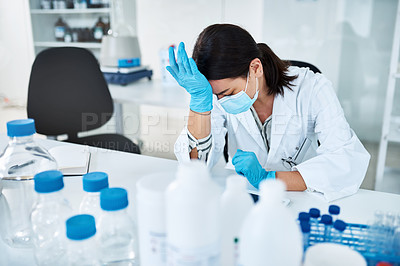 Buy stock photo Shot of a young scientist looking stressed out while working in a lab