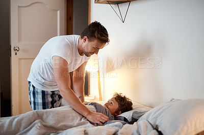 Buy stock photo Cropped shot of a man putting his son to bed