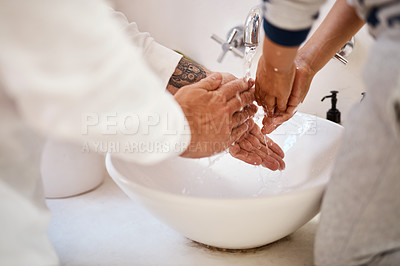Buy stock photo Cropped shot of a man and his son washing their hands in the bathroom