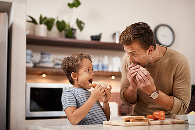 Buy stock photo Cropped shot of a man and his his having a sandwich at home