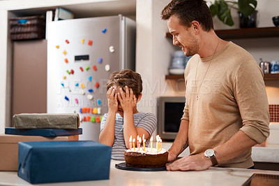 Buy stock photo Shot of a man surprising his son with cake and gifts on his birthday