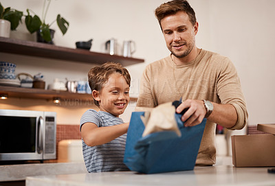 Buy stock photo Shot of a boy opening a gift from his father at home