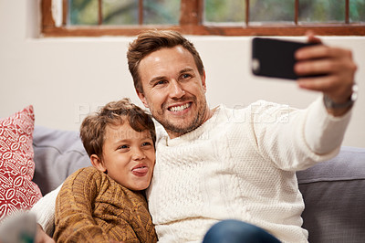 Buy stock photo Cropped shot of a man taking a selfie with his son at home