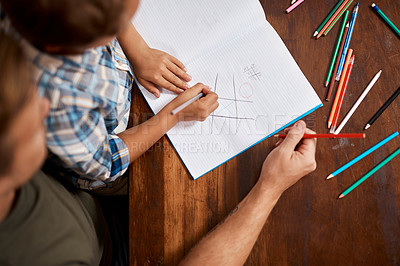 Buy stock photo Shot of a boy playing Tic-Tac-Toe with his dad at home