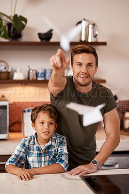 Buy stock photo Cropped shot of a man and his young son playing with paper planes at home