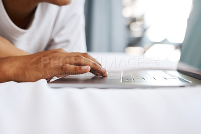 Buy stock photo Cropped shot of an unrecognizable man using his laptop while lying on his bed