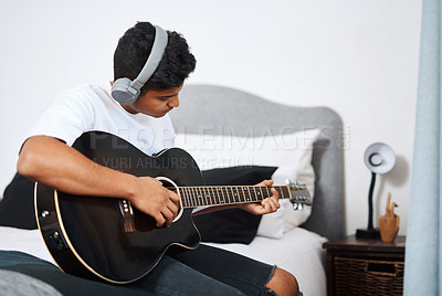 Buy stock photo Shot of a young man wearing headphones while playing the guitar at home