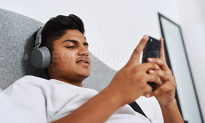 Buy stock photo Cropped shot of a young man using his cellphone while listening to music through his headphones