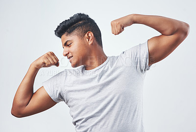 Buy stock photo Studio shot of a young man flexing against a white background