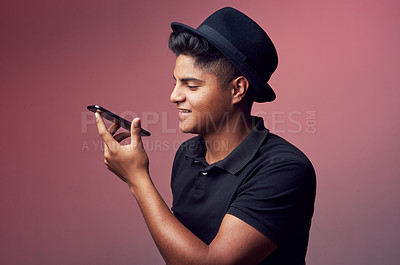 Buy stock photo Studio shot of a young man holding his cellphone