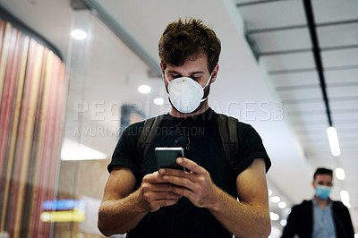 Buy stock photo Shot of a young man wearing a mask and using a smartphone in an airport