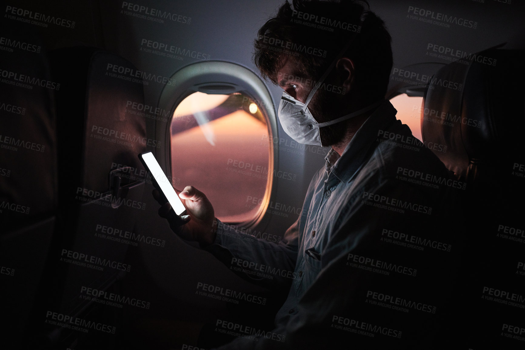 Buy stock photo Shot of a young man wearing a mask and using a smartphone in an airplane