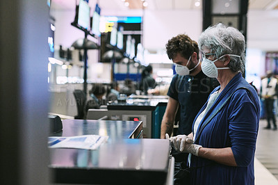 Buy stock photo Shot of a masked young man and senior woman at the check in counter of an airport