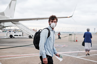 Buy stock photo Shot of a young man wearing a mask on the runway of an airport