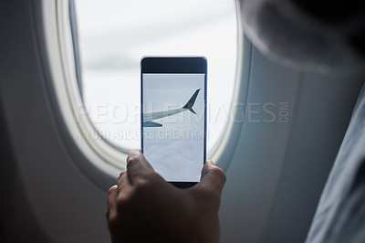Buy stock photo Cropped shot of a man using a smartphone to take pictures of the view from an airplane