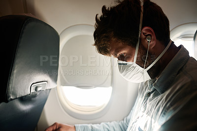 Buy stock photo Shot of a young man wearing a mask and using earphones in an airplane