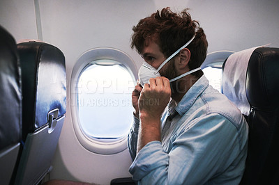 Buy stock photo Shot of a young man putting on a mask while traveling in an airplane