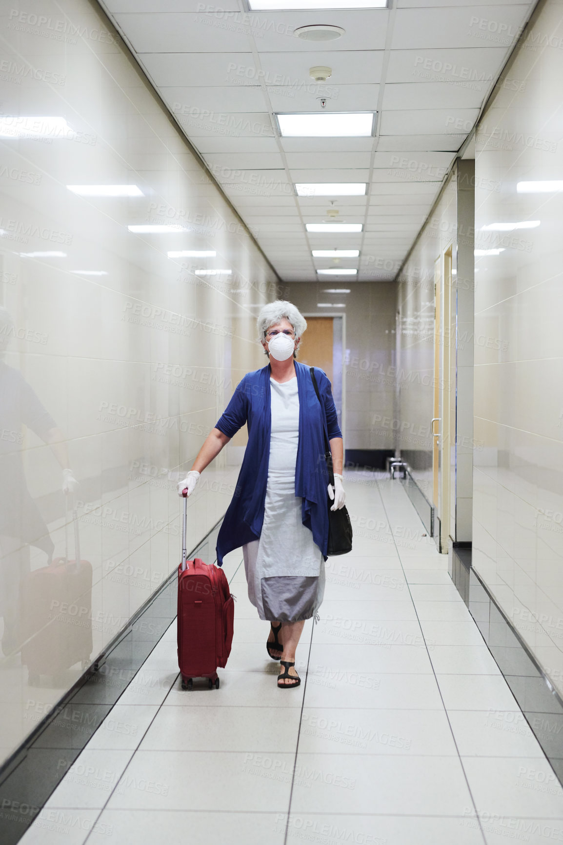Buy stock photo Shot of a senior woman wearing a mask in an airport