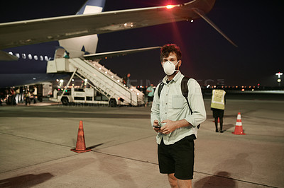 Buy stock photo Shot of a young man wearing a mask and using a smartphone on the runway at an airport