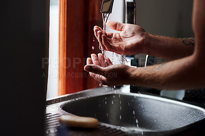 Buy stock photo Shot of an unrecognisable man washing his hands in the kitchen sink at home
