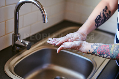 Buy stock photo Shot of an unrecognisable man washing his hands with soap in the sink at home