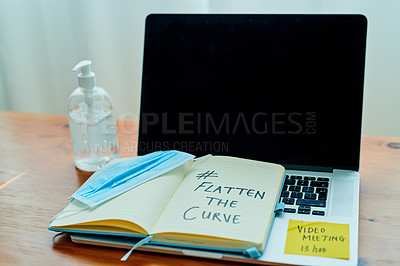 Buy stock photo Shot of a medical mask, hand sanitiser, laptop and notebook saying #FLATTEN THE CURVE on a table at home