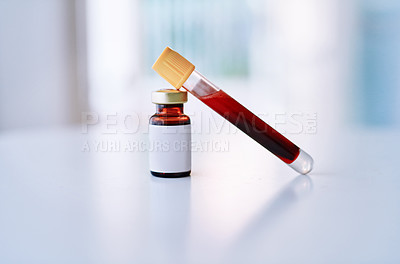 Buy stock photo Shot of a blood filled test tube and vial on a table