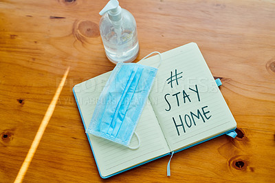 Buy stock photo Shot of a medical mask, hand sanitiser and notebook saying #STAY HOME on a table at home
