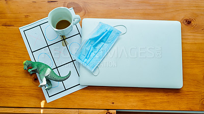 Buy stock photo High angle of a laptop, coffee, face mask, child's toy and game on a table at home