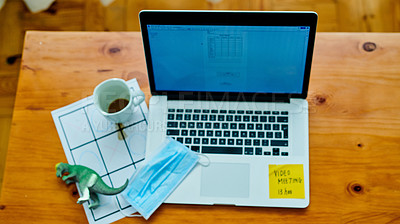Buy stock photo High angle of a laptop, face mask, coffee, child's toy and game on a table at home