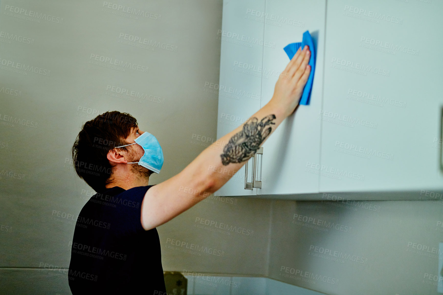 Buy stock photo Shot of a young man wearing a mask and cleaning the kitchen cupboards at home