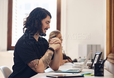 Buy stock photo Shot of a young businessman working in an office with his colleague in the background