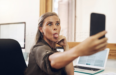Buy stock photo Shot of a young businesswoman sticking out her tongue while taking selfies in an office